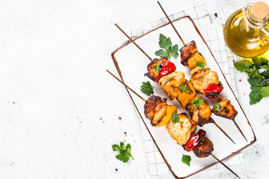 Chicken kebab on skewers on white.