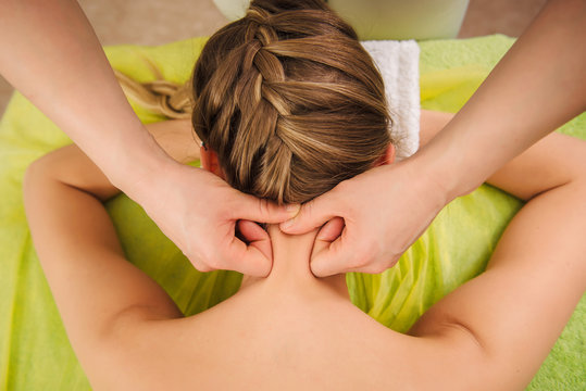 Woman having neck and shoulder massage in spa center