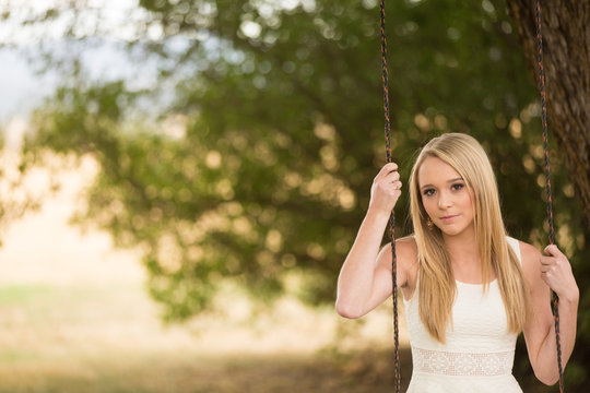 Pretty young woman sitting on rope swing
