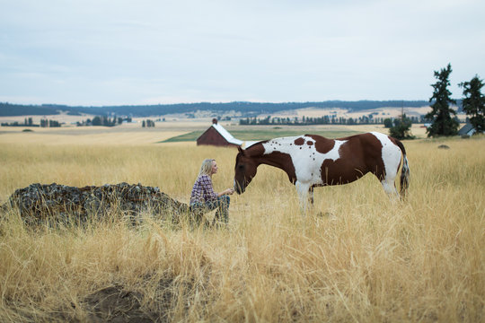 Young woman and horse in field