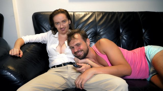 parody, humor. couple, woman androgenic feminist and man metrosexual at home on the couch communicate