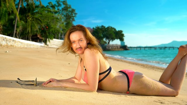 The concept of strange adventures of people. A beautiful woman in a pink bikinis on the beach, turned to the camera, and her mustache is visible on her face.