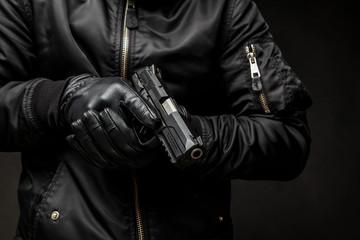 Fototapeta a man in a black jacket and black gloves holding a gun on a dark back