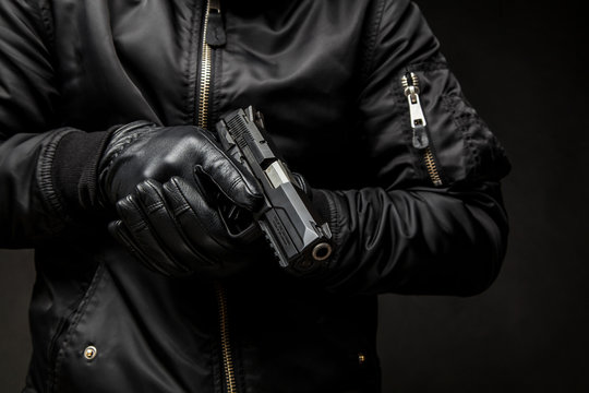 a man in a black jacket and black gloves holding a gun on a dark back