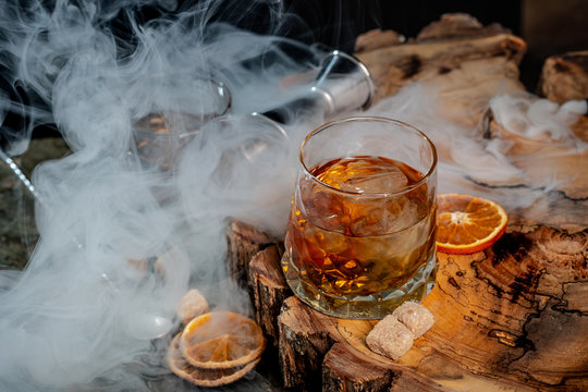 Alcohol cocktail with whiskey. Old Fashioned recipe ingredients on wooden board background.