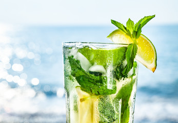 Cocktail mojito with ice and lemon on the background of the ocean closeup