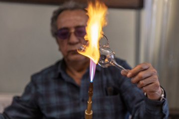 Close up macro of glass blower working with flame on a handmade wine glass from precious crystal in a workshop. Concept of handmade, high quality, artisan, made in Istanbul, Turkey, glass blowing.