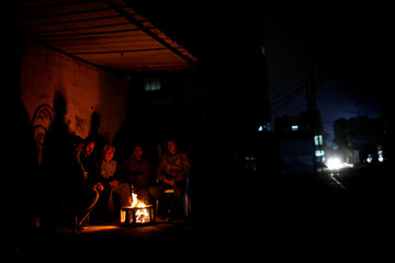 Palestinians sit around a fire to warm themselves during power cut, on a winter day in Gaza City