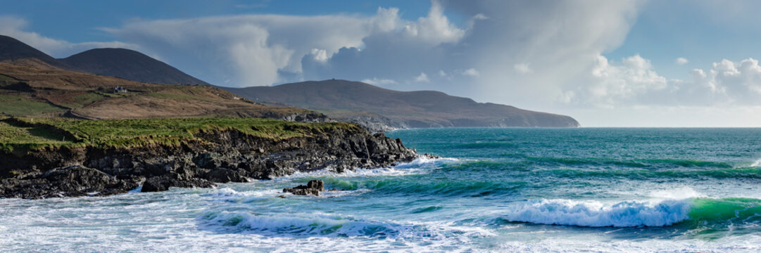 a view of the wild atlantic way off the coast of the ring of kerry in ireland showing skellig michael and surrounding islands in beautiful strong light with cloudy skies