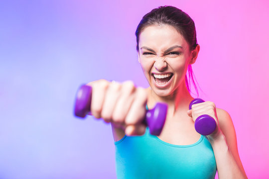 Close-up portrait of young attractive happy woman in sport clothes with beautiful smile holding weight dumbbell doing fitness workout isolated on white background in healthy lifestyle concept