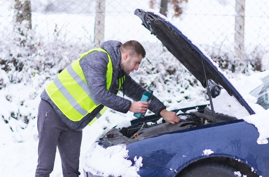 Man pouring motor oil to car engine.