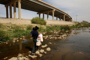 A migrant from Central America and her baby are seen at the banks of the Rio Bravo while crossing illegaly to turn themselves in to request asylum to U.S. Customs and Border Protection officials in El Paso, Texas, in this picture taken from Ciudad Juarez