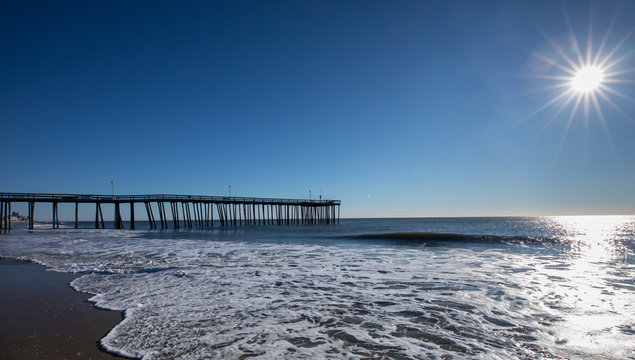 Wide view of long pier at the ocean over a sandy beach in the early morning. Photo by: Chuck Beyer