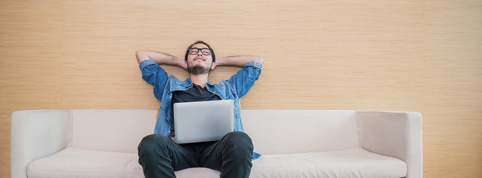 Handsome asian man relaxing with laptop on the sofa couch. Smiling longhair nerd man working with computer at home. Technology internet connection lifestyle concept banner.