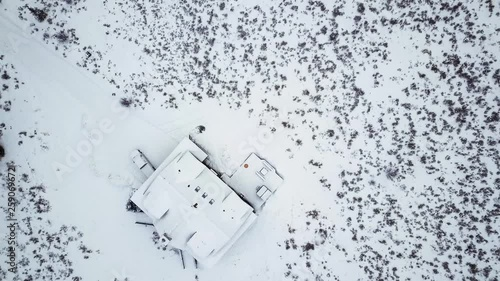 Wall mural Aerial view of the mountain house covered in snow in the Winter.