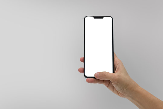 Hand holding black mobile phone with blank screen isolated on gray