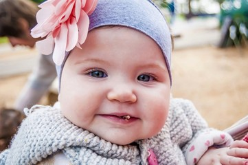 Funny, cute and adorable six or seven months old baby girl with blue eyes eating cookies with crumbs on her lips somewhere outside. Caucasian infant close up portrait. First taste. Spring or autumn