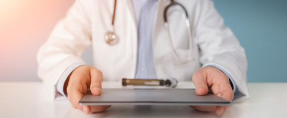 Doctor using modern tablet to read analysis results