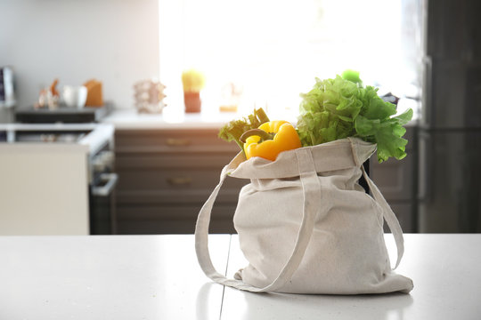 Eco bag with fresh vegetables on table in kitchen