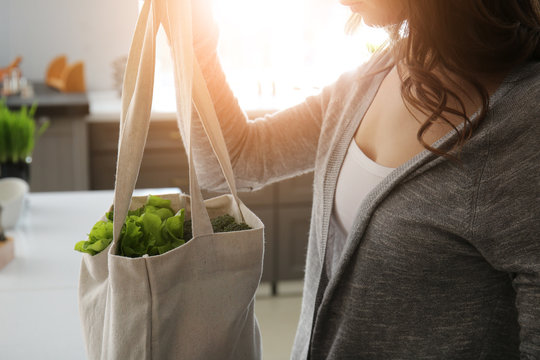 Young woman with fresh vegetables in eco bag indoors