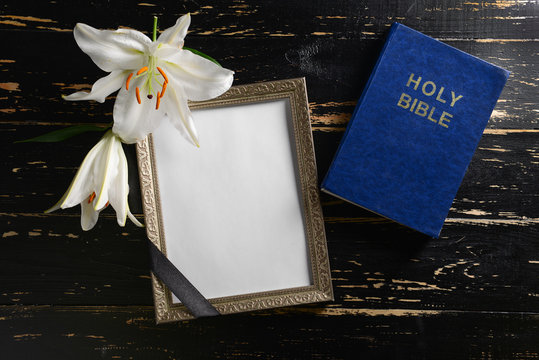 Blank funeral frame, flowers and Bible on dark wooden background