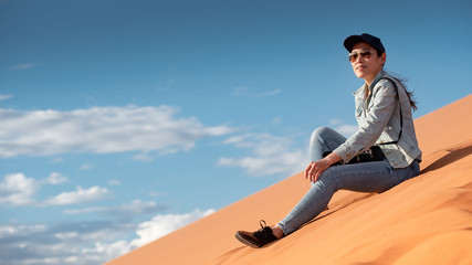 Young Asian woman traveler and photographer sitting on sand dune enjoy looking at the scenery in Namib desert of Namibia, Africa. Travel photography concept