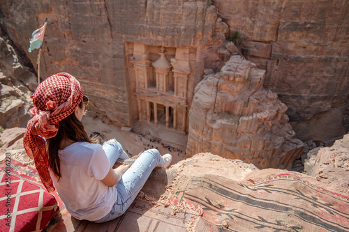 competitive price 20040 a47e1 Asian woman traveler sitting on carpet viewpoint in Petra ancient city  looking at the Treasury or Al-khazneh, famous travel destination of Jordan  and one of ...