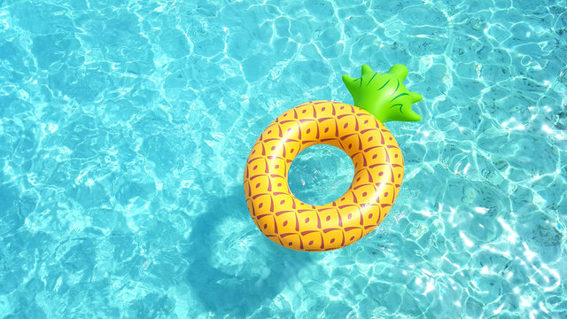 Pineapple life ring floating in crystal blue sea water on a sunny day for relaxation and happy summer holiday vacations concept.