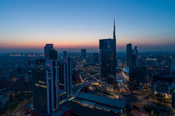 Milan (Italy) city skyline at dawn, aerial view, flying over financial area skyscrapers in Porta Nuova district. Unicredit Tower office building at sunrise.