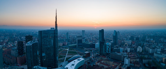 Photo sur Plexiglas Milan Milan (Italy) city skyline at dawn, aerial view, flying over financial area skyscrapers in Porta Nuova district. Unicredit Tower office building at sunrise.