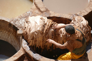 Workers prepare hides in pits of the leather tannery
