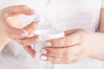 Adult woman hands applying moisturizing cream to her skin