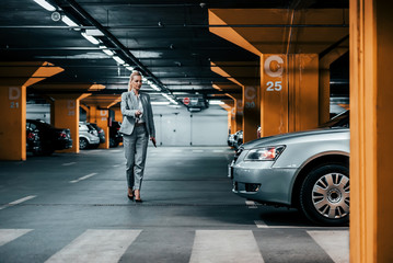 Successful businesswoman walking to her car in underground car parking. Wall mural