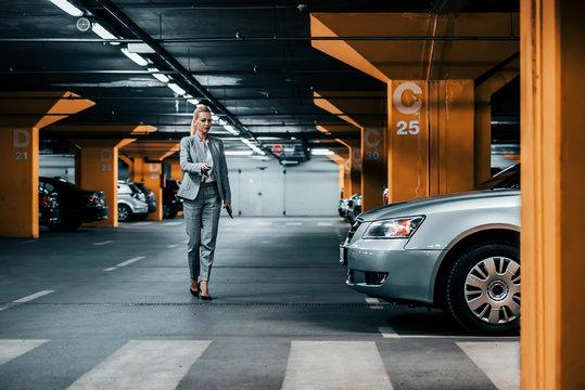 Successful businesswoman walking to her car in underground car parking.