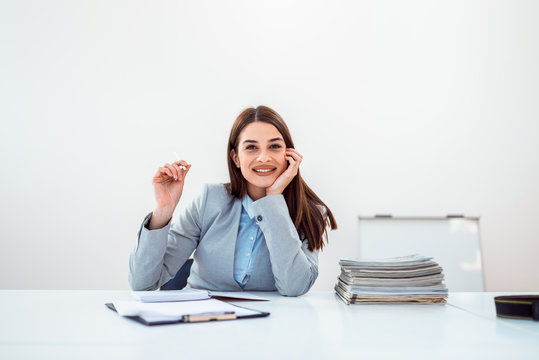 Cute business woman in bright office with papers.