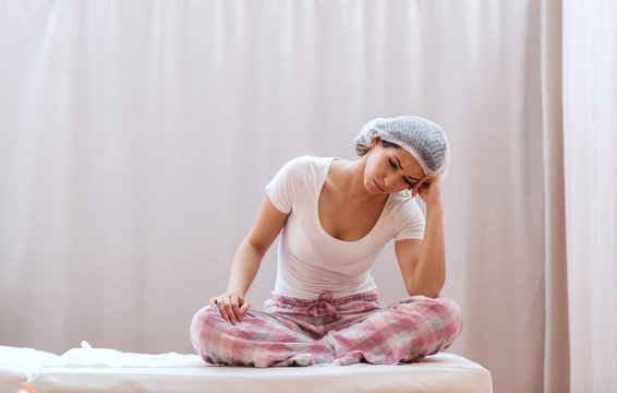 Worried female patient in pajamas and with medical cap waiting for surgery with legs crossed.