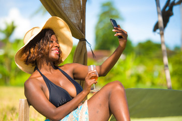 attractive black African American woman in bikini taking selfie picture with mobile phone for internet social media relaxed at tropical beach resort drinking glass of wine