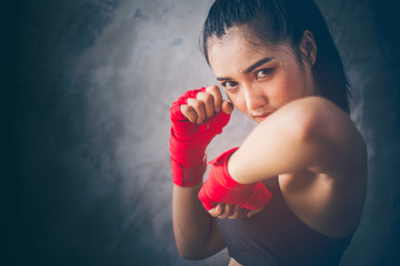 Beautiful young Asian boxers. She is a martial arts athlete, strong face filled with sweat, her eyes are committed. Two of her hands with red boxing bandage hand wrap. Woman power with copy space.