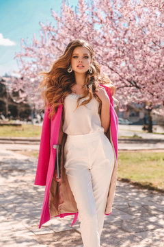 beautiful young girl with natural hair color in elegant clothes posing among flowering peach trees