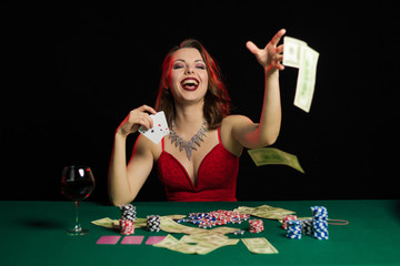 Emotional young lady in an evening red dress playing cards on a table on green cloth in a casino