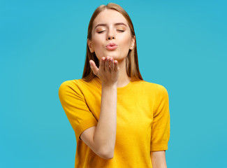 Charming young girl with closed eyes sends air sweet kiss. Photo of girl with natural makeup in yellow sweater on blue background.