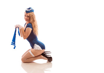Young blonde girl in blue suit and stockings in pin-up style poses against white background