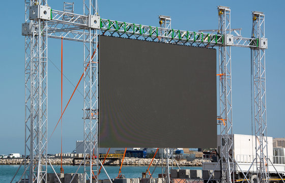 Big open-air black outdoor LED screen for public music event at sea shore, copyspace