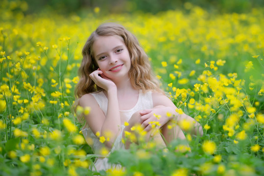 A cute young girl is in the forest on the edge of the forest with yellow flowers. She has blond curly hair, she's wearing a beautiful dress.