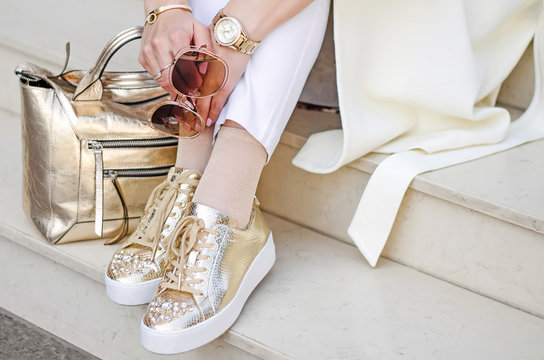 Golden sneakers, bag and watch closeup. Sunglasses closeup in female hands. The girl sits on the steps.