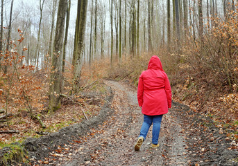 Woman in a red cape hiking in a forest
