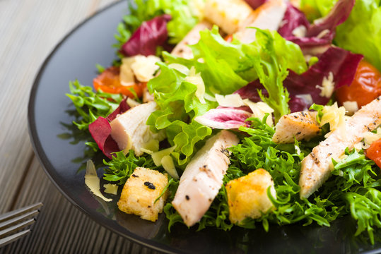 Healthy chicken salad with lettuce, grilled tomato, croutons, shredded cheese and grilled chicken