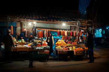 Night scene on the streets of Tbilisi, Georgia. Street sellers around corner selling traditional Georgian products with customers passing by. - Night image