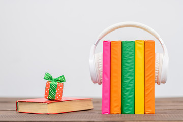 Books with white  headphones and gift box. Audiobooks concept. Empty space for text