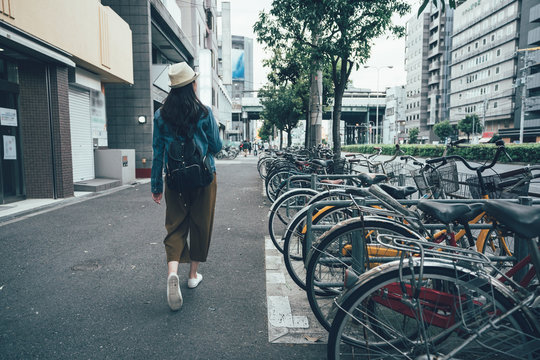 Parking for bicycles on the street rent a bike and walking around city in osaka japan. back view full length young asian woman in hat sightseeing busy urban residential area. female relax sunny day